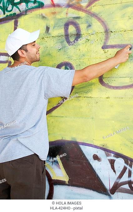 Rear view of a young man making a graffiti on a wall