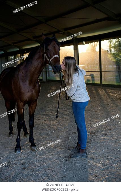 Young woman kissing horse in riding arena