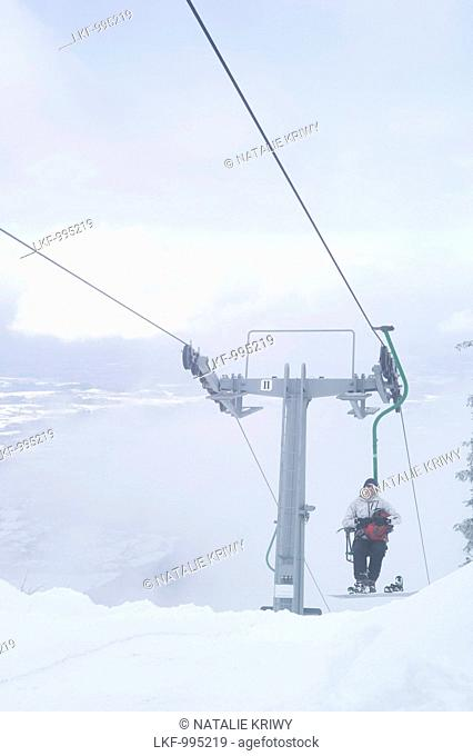 Snowboarder in a single chair lift, Kampenwand, Alps, Bavaria, Germany