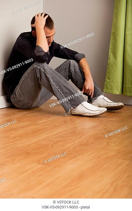 USA, Illinois, Metamora, Depressed man sitting on floor in empty room