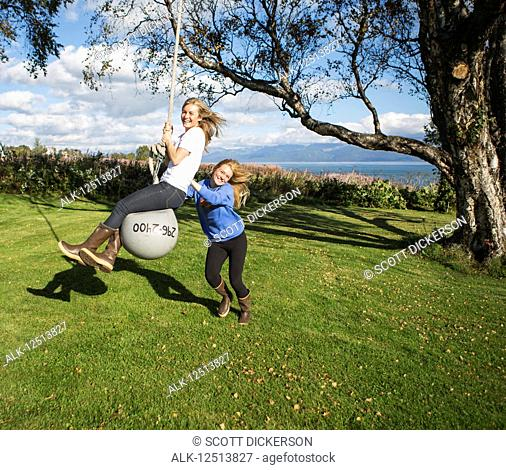 Two young women playing on a buoy rope swing, South-central Alaska; Homer, Alaska, United States of America
