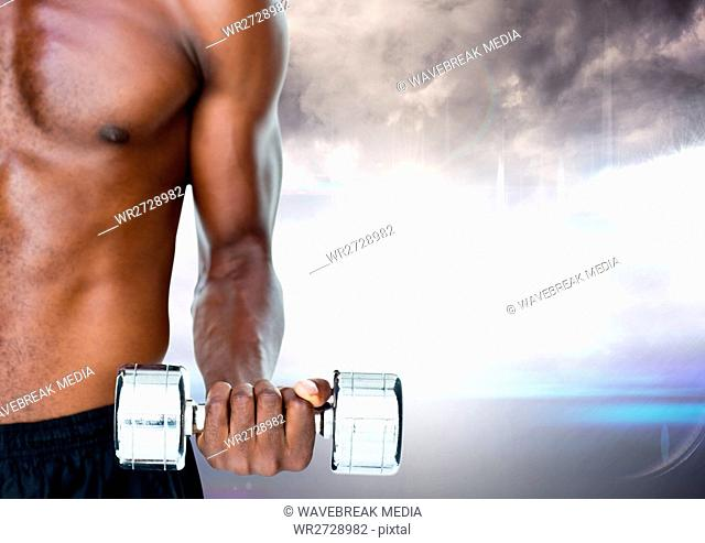 Composite image of mid section of a fit man lifting dumbbells