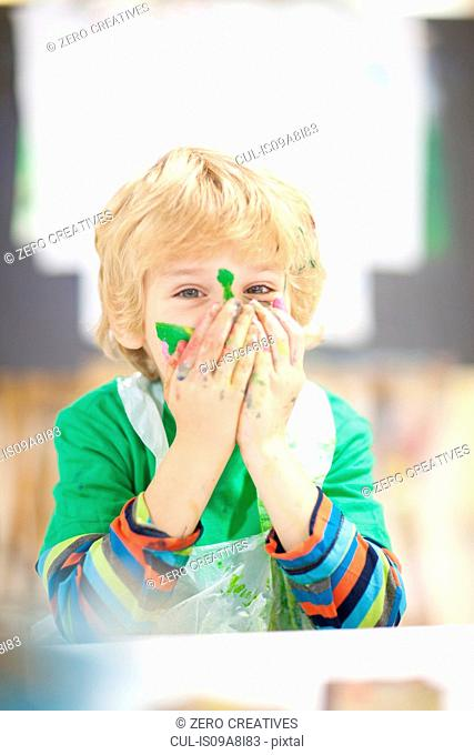 Boy with paint on his face and hands over mouth
