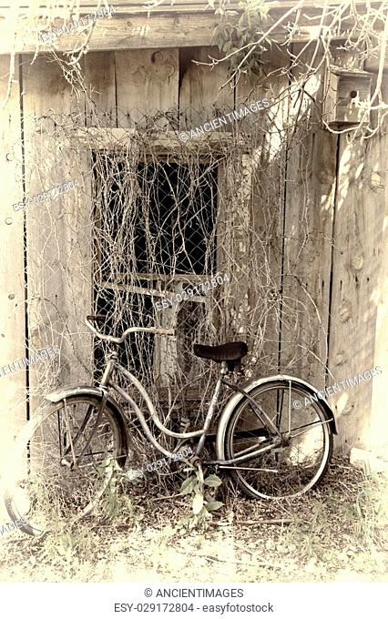 Old, antique bicycle leans against abandoned building with broken window