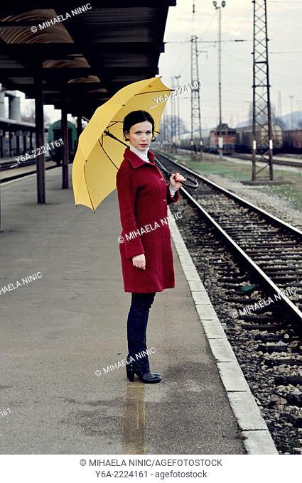 Mid adult woman standing on railroad station platform holding umbrella