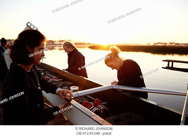 Female rowers preparing scull at sunrise lakeside