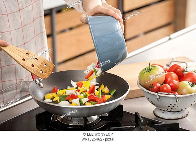 a woman cooking vegetables