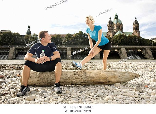Young couple stretching on the waterfront, Munich, Bavaria, Germany