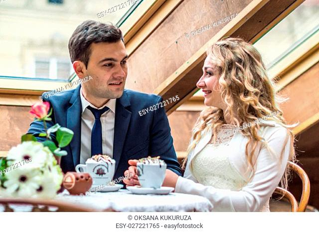 newly married couple drinking coffee in a cafe