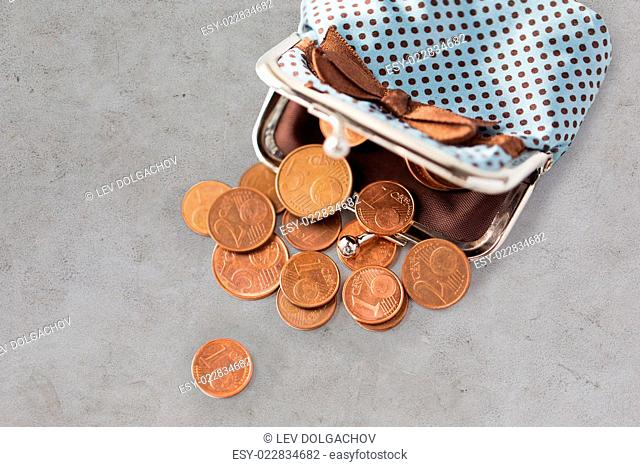 finance, cash, money saving and investment concept - close up of euro coins and wallet on gray concrete table