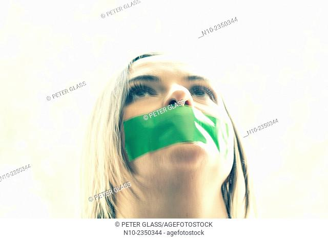 Young woman with tape over her mouth