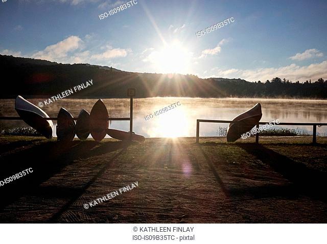 Canoes leaning against railing beside lake, Arrowhead Provincial Park, Ontario, Canada