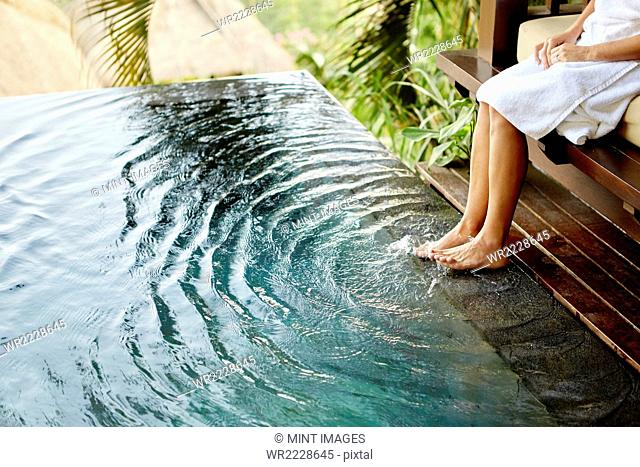 A person sitting on a bench with her feet in the shallow water of a pool, making ripples