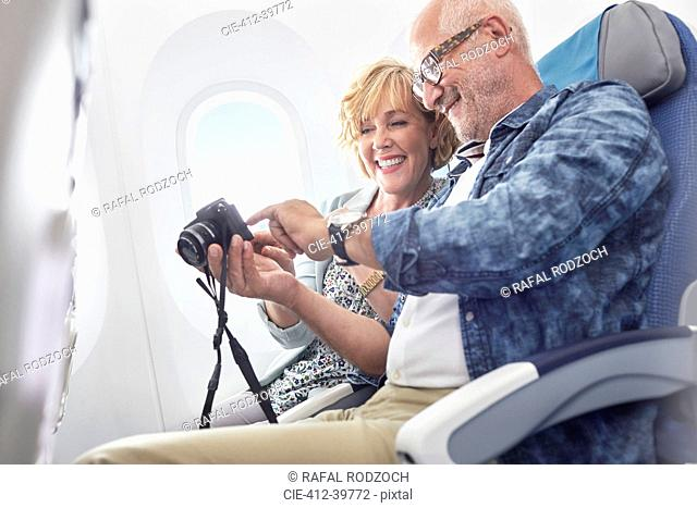 Mature couple looking at photos on digital camera on airplane