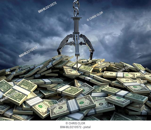 Claw grabbing at bundles of one dollar bills