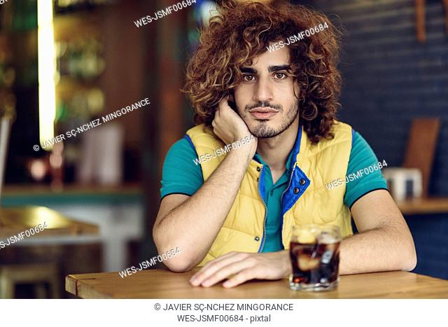 Portrait of young man with beard and curly hair drinking cola in a pub