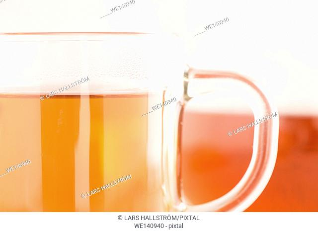 Tea in glass cup. Detail of hot drink. Concept of warm beverage, breakfast or teatime