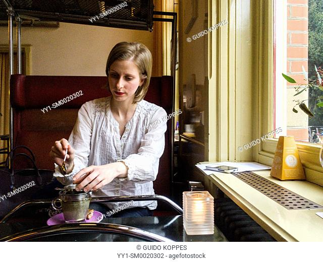 Tilburg, Netherlands. Caucasian female preparing her cup of tea while visiting a cafe for a meeting