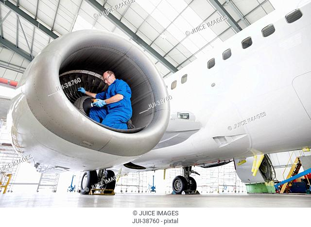 Engineer testing engine of passenger jet in hangar