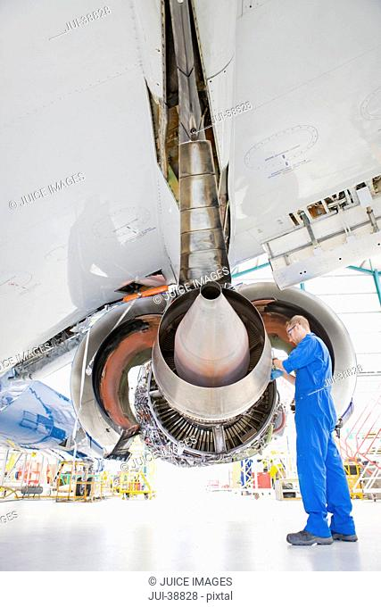 Engineer working under wing of passenger jet in hangar