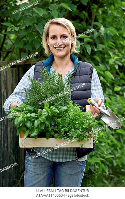 Woman in the garden with a basket full of herbs