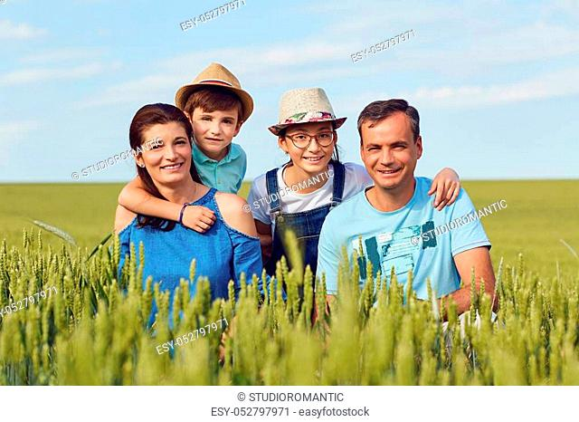 Portrait of a happy family sitting on nature in the grass in summer
