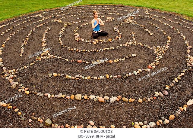 Woman meditating in stone labyrinth