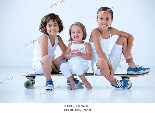three young girls sitting on a long board