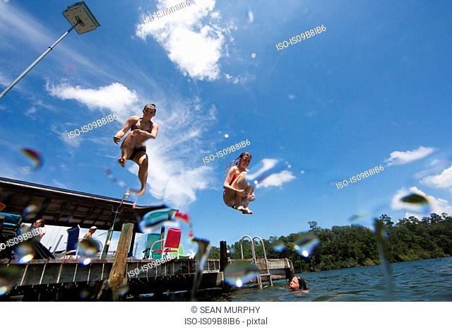 Teenagers jumping into lake, low angle view