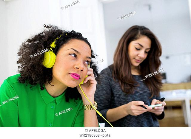 Young businesswoman using headphones while colleague holding adhesive note in office