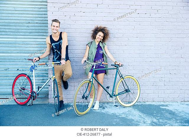 Portrait young man and young woman with bicycles at urban wall