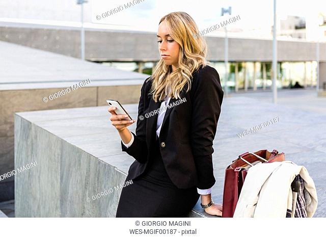 Businesswoman looking at cell phone