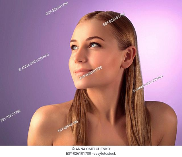 Portrait of beautiful woman with natural makeup looking up over purple background, perfect clear skin, beauty treatment concept