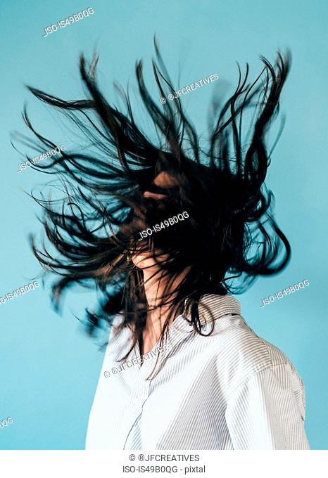 Young woman with long hair, tossing head back