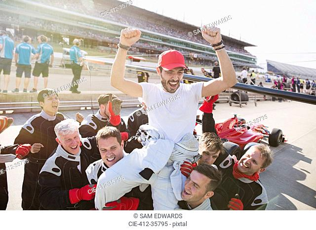 Formula one racing team carrying driver on shoulders, celebrating victory on sports track