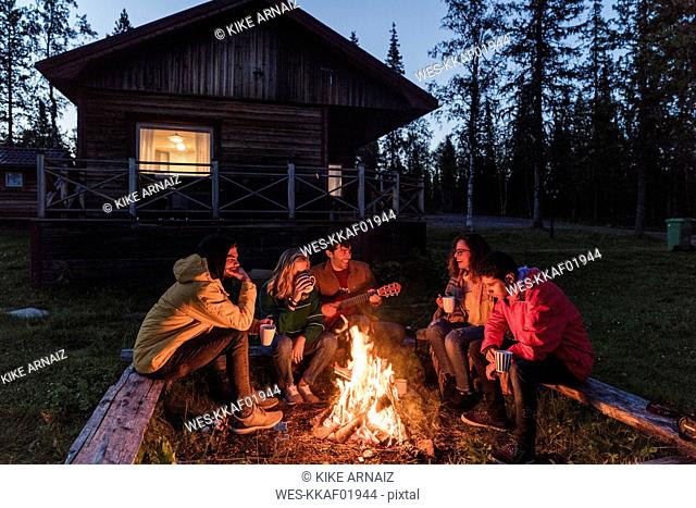 Group of friends sitting at a campfire, talking and playing guitar