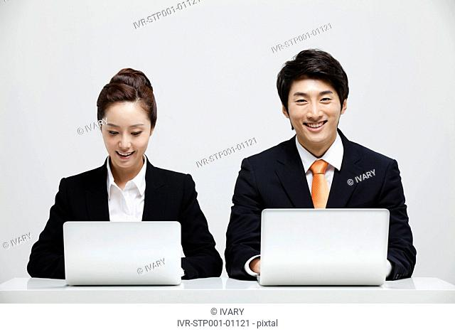 Asian Businessman And Businesswoman Sitting At Desk With Laptop