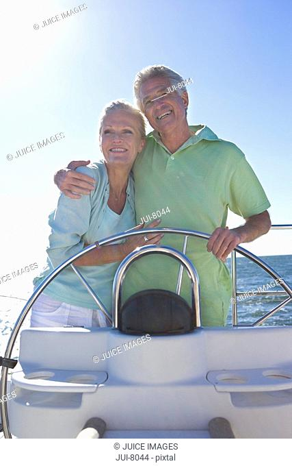 Mature couple standing at helm of yacht out at sea, arms around each other, man steering, smiling, front view, portrait backlit