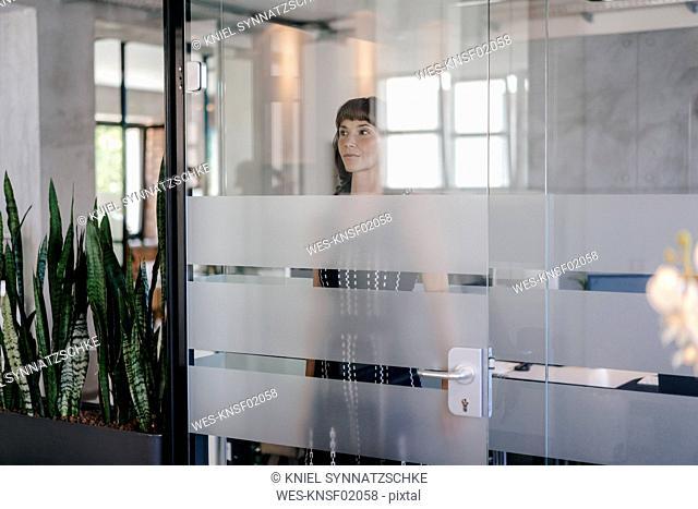 Businesswoman standing behind glass door