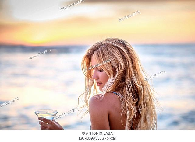 Young woman on beach drinking cocktail at sunset
