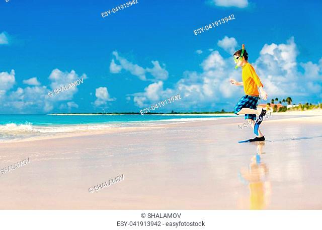 Cute boy wearing mask, snorkel and fins walking at tropical beach having fun summer vacation