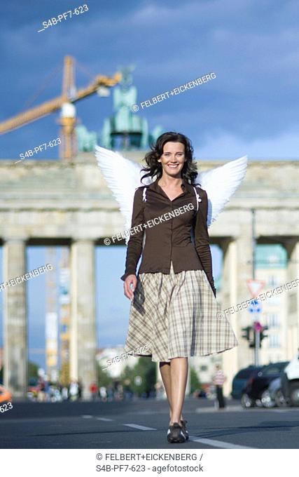 Woman with angel wings at Brandenburg Gate, Berlin, Germany