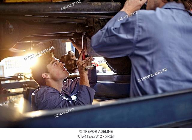 Mechanics working under car in auto repair shop
