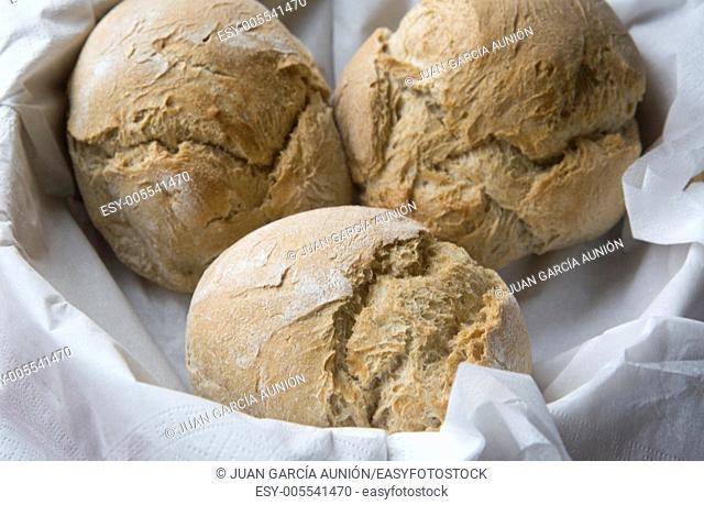 A wooden basket of freshly rolls btween white napkins, Spain