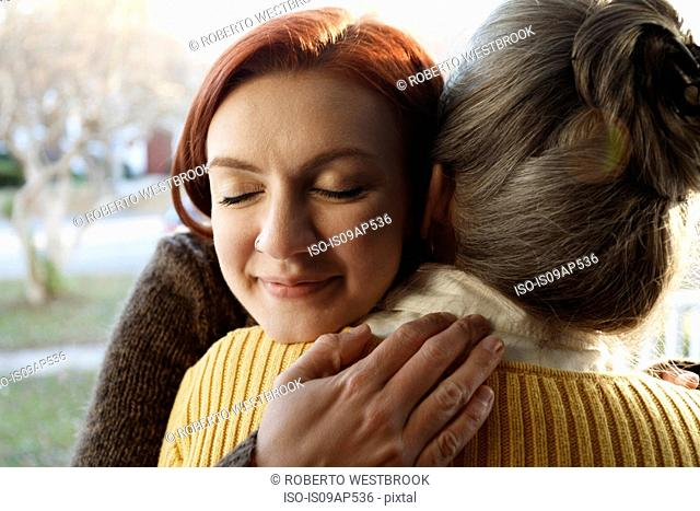 Close up of senior woman and adult daughter hugging on porch
