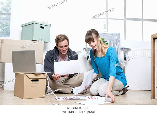 Two colleagues sitting on ground between cardboard boxes in an office