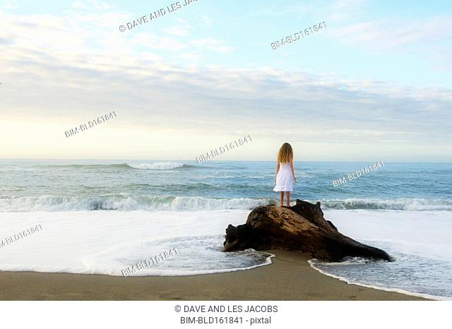 Mixed race girl standing on rock at beach
