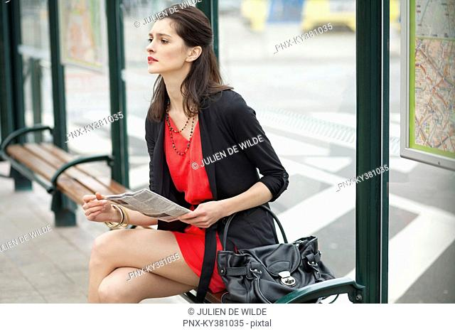 Woman sitting at a bus stop and holding a newspaper