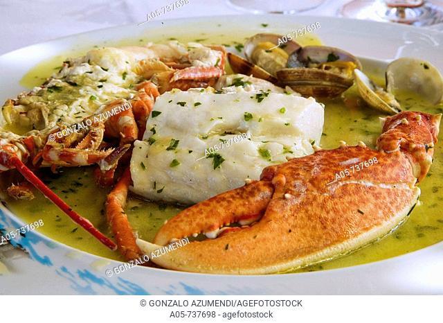 Hake and lobster in green sauce at El Puerto restaurant, Gijon. Asturias, Spain