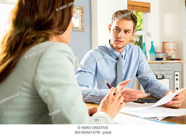 Young man at kitchen table explaining bills to girlfriend